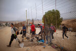 FILE - In this Sunday, Sept. 6, 2020 file photo, Palestinian laborers some wearing protective face masks amid concerns over the country's coronavirus outbreak, cross illegally into Israel from the West Bank through an opening in a fence, south of the West Bank town of Hebron. Israel's premier human rights group has begun describing both Israel and its control of the Palestinian territories as a single