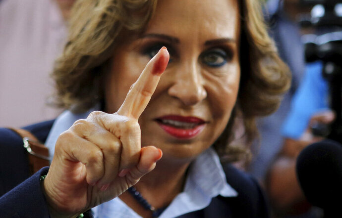 Sandra Torres, presidential candidate of the National Unity of Hope party, UNE, shows her ink stained finger to the press after casting her vote during general elections in Guatemala City, Sunday, June 16, 2019. Guatemalans are voting for their next president in elections plagued by widespread disillusion and distrust, and as thousands of their compatriots flee poverty and gang violence to seek a new life in the United States. The former first lady is expected to finish first but without enough votes to win in the first round.  (AP Photo/Oliver de Ros)