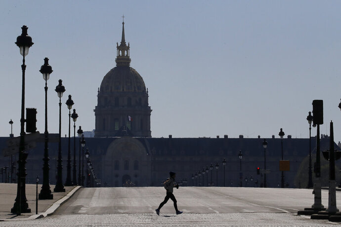 A man jogs in an empty Paris street, Wednesday, March 25, 2020. French President Emmanuel Macron urged employees to keep working in supermarkets, production sites and other businesses that need to keep running amid stringent restrictions of movement due to the rapid spreading of the new coronavirus in the country. The new coronavirus causes mild or moderate symptoms for most people, but for some, especially older adults and people with existing health problems, it can cause more severe illness or death. (AP Photo/Christophe Ena)