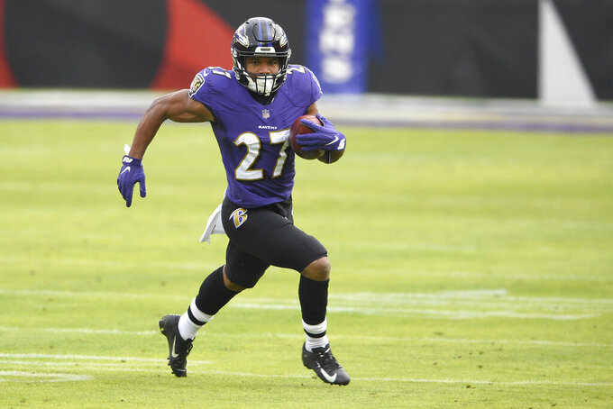 Baltimore Ravens running back J.K. Dobbins runs with the ball against the Jacksonville Jaguars during the first half of an NFL football game, Sunday, Dec. 20, 2020, in Baltimore. (AP Photo/Nick Wass)