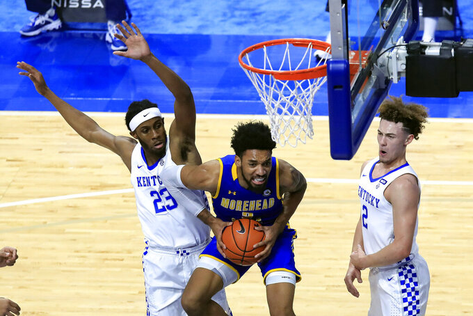 Morehead State's James Baker, middle, looks for a shot between Kentucky's Isaiah Jackson, left, and Devin Askew during the first half of an NCAA college basketball game in Lexington, Ky., Wednesday, Nov. 25, 2020. (AP Photo/James Crisp)
