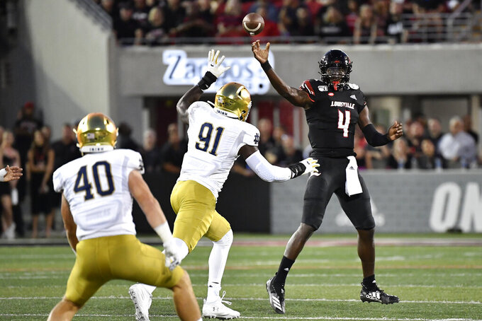 Louisville quarterback Jawon Pass (4) attempts a pass over the defense of Notre Dame defensive lineman Adetokunbo Ogundeji (91) and Drew White during the first half of an NCAA college football game in Louisville, Ky., Monday, Sept. 2, 2019. (AP Photo/Timothy D. Easley)