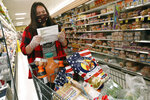 Alexandra Lopez-Djurovic checks her shopping list as she shops for a client in an Acme supermarket, Wednesday, July 1, 2020, in Bronxville, N.Y. Lopez-Djurovic was working full time as a nanny until her hours were cut substantially due to the coronavirus pandemic, so she started her own grocery delivery service that made up for some of her lost wages, but not all. (AP Photo/Kathy Willens)