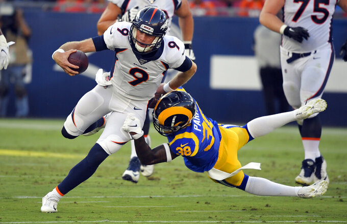 Denver Broncos quarterback Kevin Hogan (9) is tackled by Los Angeles Rams defensive back Steven Parker during the first half of an NFL preseason football game Saturday, Aug. 24, 2019, in Los Angeles. (AP Photo/Mark J. Terrill)