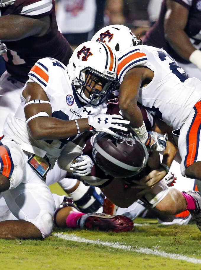 Auburn defensive backs Daniel Thomas, left, and Jeremiah Dinson, fail from keeping Mississippi State quarterback Nick Fitzgerald, underneath, from scoring on a one-yard dive into the end zone during the first half of their NCAA college football game in Starkville, Miss., Saturday, Oct. 6 2018. (AP Photo/Rogelio V. Solis)