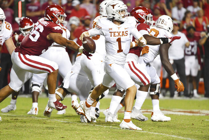 Arkansas defender Zach Williams (56) knocks the ball out of the hand of Texas quarterback Hudson Card (1) during the second half of an NCAA college football game Saturday, Sept. 11, 2021, in Fayetteville, Ark. Arkansas recovered the ball. (AP Photo/Michael Woods)