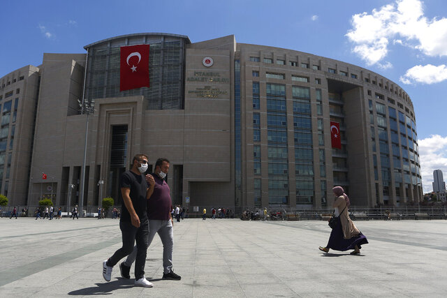 People walk outside a court in Istanbul, Thursday, July 16, 2020, where the trial of Deniz Yucel, a German-Turkish journalist, accused of terror charges was held. The court convicted Yucel on charges of engaging in propaganda in favor of Kurdish rebels, and sentenced him to two years and nine months in prison. (AP Photo/Mehmet Guzel)