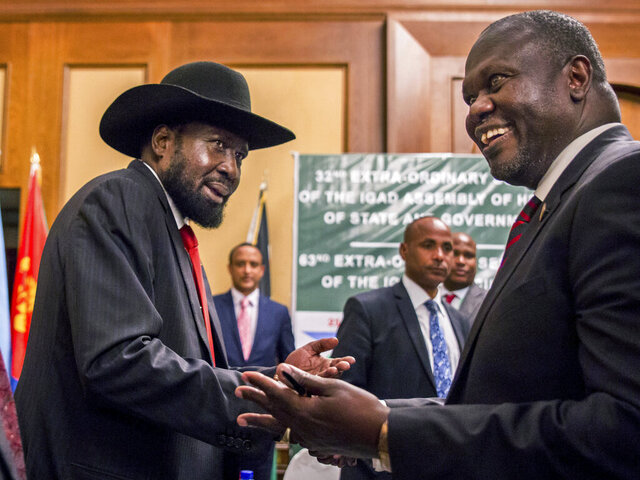 FILE - In this Thursday, June 21, 2018 file photo, South Sudan's President Salva Kiir, left, and opposition leader Riek Machar shake hands during peace talks in Addis Ababa, Ethiopia.  South Sudan rival leaders on Thursday Feb. 20, 2020, announced they have agreed to form a coalition government. (AP Photo/Mulugeta Ayene, File)