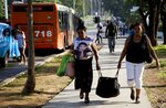 Women carry a bag after arriving by bus to Havana, Cuba, Thursday, June 27, 2019. Cuban President Miguel Díaz-Canel says the country's governing council has approved economic measures including a rise in state salaries, long seen as a first step toward ending the country's dual-currency system which is expected to create a chain reaction that includes higher inflation. (AP Photo/Ismael Francisco)