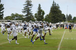 The Los Angeles Rams warm up during NFL football training camp Wednesday, Aug. 7, 2019, in Napa, Calif. Both the Oakland Raiders and the Los Angeles Rams held a joint practice before their upcoming preseason game on Saturday. (AP Photo/Eric Risberg)
