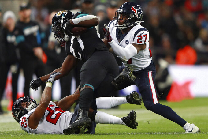 Houston Texans free safety Mike Adams (27) hits Jacksonville Jaguars running back Leonard Fournette (27) during the second half of an NFL football game at Wembley Stadium, Sunday, Nov. 3, 2019, in London. (AP Photo/Ian Walton)