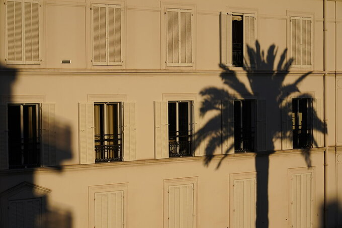 The reflection of a palm tree on a building as the sun sets at the 74th international film festival, Cannes, southern France, Thursday, July 8, 2021. (AP Photo/Brynn Anderson)