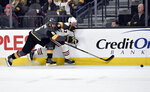 Vegas Golden Knights defenseman Deryk Engelland (5) and Chicago Blackhawks left wing Lance Bouma chase down the puck during the first period of an NHL hockey game Tuesday, Feb. 13, 2018, in Las Vegas. (AP Photo/David Becker)