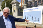 David Stevenson, policy director at the Caesar Rodney Institute, points to a placard that features images of landmarks and a wind turbine, while facing reporters Wednesday, Aug. 25, 2021, in front of the Statehouse, in Boston. A group from the island of Nantucket, Mass., called ACK Residents Against Turbines, filed a federallawsuitWednesday to block the construction of dozens of wind turbines off the coast of Nantucket and nearby island of Martha's Vineyard. The group says Vineyard Wind's proposed project poses a risk to the endangered Northern Atlantic right whale. (AP Photo/Philip Marcelo)
