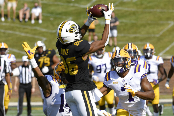 Missouri wide receiver Tauskie Dove (86) catches an 86-yard pass for a touchdown as LSU safety Maurice Hampton Jr., left, and safety JaCoby Stevens, right, defend during the first half of an NCAA college football game Saturday, Oct. 10, 2020, in Columbia, Mo. (AP Photo/L.G. Patterson)
