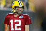 Green Bay Packers quarterback Aaron Rodgers smiles as he walks off the field during NFL football training camp at Lambeau Field on Saturday, Aug. 7, 2021, in Green Bay, Wis. (AP Photo/Matt Ludtke)