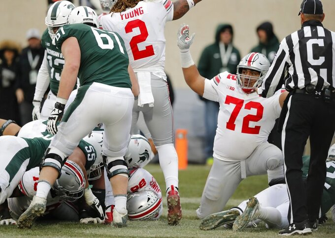 Ohio State defensive tackle Tommy Togiai (72) reacts after teammate defensive tackle Dre'Mont Jones (86) recovers a fumble at the 2-yard line during the second half of an NCAA college football game, Saturday, Nov. 10, 2018, in East Lansing, Mich. (AP Photo/Carlos Osorio)