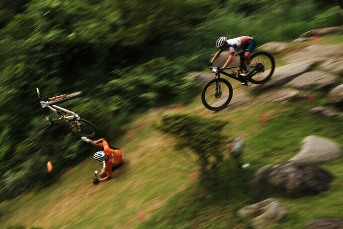 Mathieu van der Poel of the Netherlands tumbles on a downhill during the men's cross country mountain bike competition at the 2020 Summer Olympics, Monday, July 26, 2021, in Izu, Japan. (AP Photo/Thibault Camus)