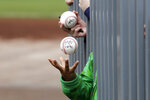 A child tosses an already-autographed baseball while awaiting another signature from a passing player before a spring training baseball game between the Los Angeles Angels and the Seattle Mariners on Tuesday, March 10, 2020, in Peoria, Ariz. (AP Photo/Elaine Thompson)