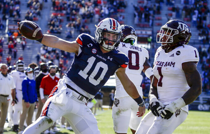Auburn quarterback Bo Nix (10) carries the ball in for a touchdown as Texas A&M linebacker Buddy Johnson (1) defends during the second half of an NCAA college football game on Saturday, Dec. 5, 2020, in Auburn, Ala.  (AP Photo/Butch Dill)