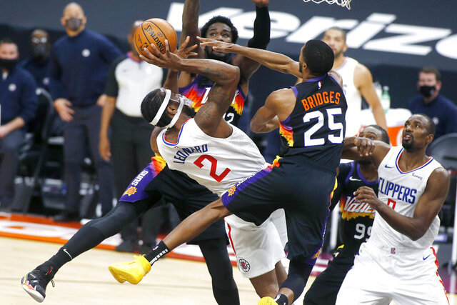 Los Angeles Clippers forward Kawhi Leonard (2) shoots over the defense of Phoenix Suns forward Mikal Bridges (25) and center Deandre Ayton (22) during the first half of an NBA basketball game Sunday, Jan. 3, 2021, in Phoenix. (AP Photo/Ralph Freso)