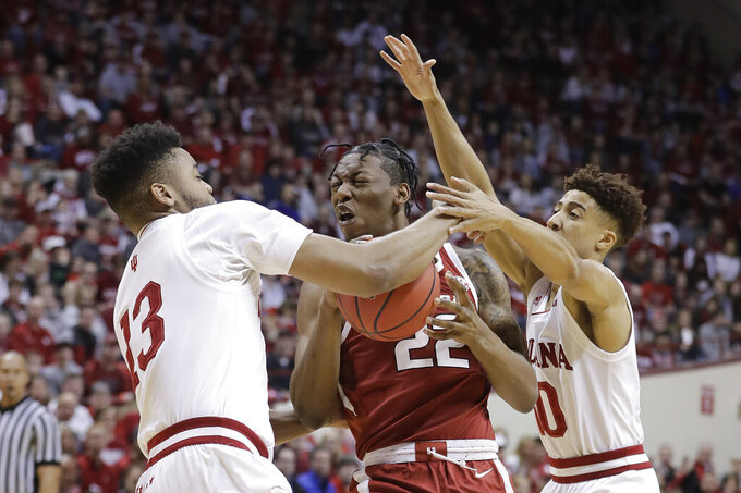 Arkansas's Gabe Osabuohien (22) is defended by Indiana's Juwan Morgan (13) and Rob Phinisee (10) during the first half in the second round of the NIT college basketball tournament, Saturday, March 23, 2019, in Bloomington, Ind. (AP Photo/Darron Cummings)
