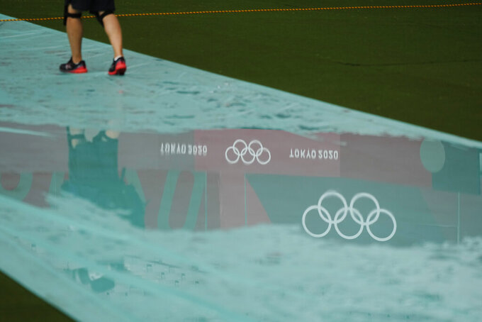 The Olympic Rings are reflected in a puddle on the women's rugby sevens pitch at the 2020 Summer Olympics, Friday, July 30, 2021 in Tokyo, Japan. (AP Photo/Shuji Kajiyama)
