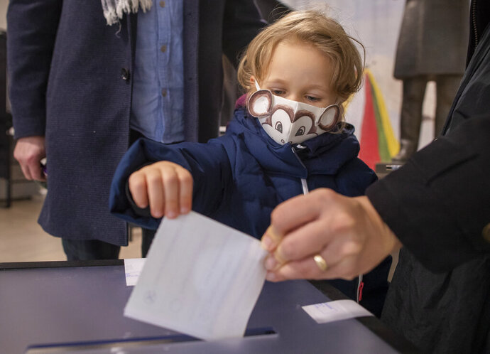 A woman with a child casts her ballot at a polling station during the second round of a parliamentary election in Vilnius, Lithuania, Sunday, Oct. 25, 2020. Polls opened Sunday for the run-off of national election in Lithuania, where the vote is expected to bring about a change of government following the first round, held on Oct. 11, which gave the three opposition, center-right parties a combined lead. (AP Photo/Mindaugas Kulbis)
