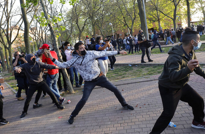 Protesters throw stones at far-right Vox supporters during a party rally in Madrid's Vallecas neigborhood, a traditional left-wing bastion, Spain, Wednesday, April 7, 2021. Scuffles started when the national leader of Vox, Santiago Abascal, approached a crowd which had gathered to protest the party rally. Riot peace charged the bunches of protesters to keep them away from Abascal and other members of his party campaigning for upcoming regional elections in the area including Spain's capital. (AP Photo/Bernat Armangue)
