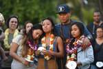 In this Tuesday, Jan. 21, 2020, photo, John Enriquez, center right, ex-husband of Honolulu Police Officer Tiffany Enriquez, holds their daughters Teiya Enriquez Sandoval, from bottom left, Jazzy and Triniti during a candlelight vigil in remembrance of Tiffany Enriquez in Honolulu. A handyman's landlord had recently started an eviction process before he stabbed a woman Sunday and fatally shot two Honolulu officers, including Enriquez. (Bruce Asato/Honolulu Star-Advertiser via AP)