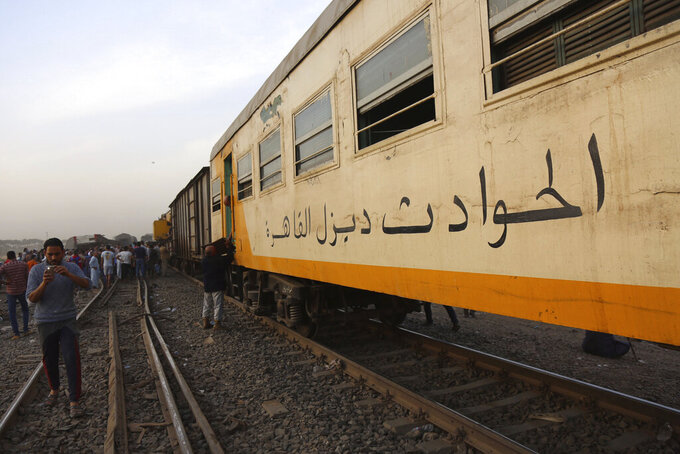 People take photos with their mobile phones at the site of a passenger train that derailed injuring some 100 people, near Banha, Qalyubia province, Egypt, Sunday, April 18, 2021. At least eight train wagons ran off the railway, the provincial governor's office said in a statement. (AP Photo/Fadel Dawood)