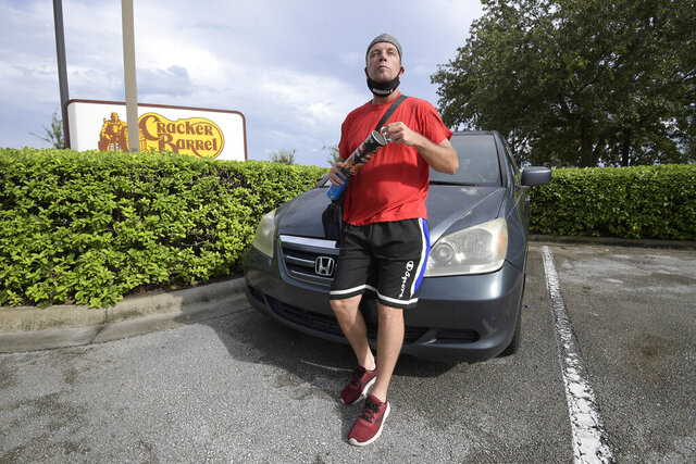 Jeff Lello stands in front of the van in which he lives, in the parking lot of a Cracker Barrel restaurant, since being laid off due to the coronavirus pandemic, Friday, Aug. 21, 2020, in Orlando, Fla. Lello is one of an estimated 20 million Americans living paycheck to paycheck, spending more than 30% of their income on rent, who are likely to experience homelessness at some point, according to the National Coalition for the Homeless. (AP Photo/Phelan M. Ebenhack)