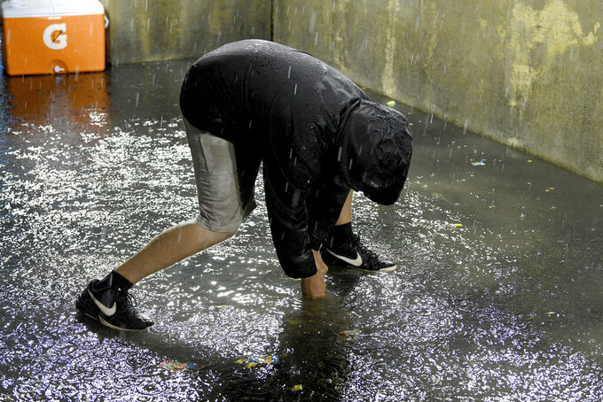A member of the Detroit Tigers grounds crew works to clear the drain in the Milwaukee Brewers dugout during a weather delay at a baseball game in Detroit, Tuesday, Sept. 14, 2021. (AP Photo/Lon Horwedel)