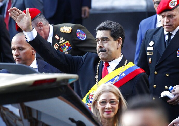 Venezuela's President Nicolas Maduro, accompanied by first lady Cilia Flores, waves to supporters as he leaves the National Pantheon after attending a ceremony to commemorate an 1800's independence battle, in Caracas, Venezuela, Wednesday, Aug. 7, 2019. Sweeping new U.S. sanctions freeze all of the Maduro government's assets in the U.S. and even threaten to punish companies from third countries that keep doing business with his socialist administration. (AP Photo/Leonardo Fernandez)