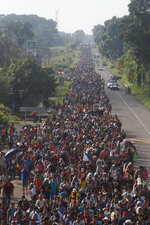 Central American migrants walking to the U.S. start their day departing Ciudad Hidalgo, Mexico, Sunday, Oct. 21, 2018. Despite Mexican efforts to stop them at the border, a growing throng of Central American migrants resumed their advance toward the U.S. border early Sunday in southern Mexico. Their numbers swelled to about 5,000 overnight. (AP Photo/Moises Castillo)