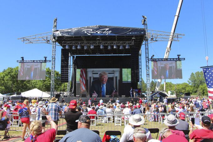 Former President Donald Trump addresses the crowd via video Saturday, June 12, 2021, at the River's Edge Apple River Concert Venue in New Richmond, Wis. The MAGA rally was organized by pillow salesman-turned conspiracy peddler Mike Lindell. For a few hours last weekend, thousands of Donald Trump's loyal supporters came together under the blazing sun in a field in western Wisconsin to live in an alternate reality where the former president was still in office — or would soon return. (AP Photo/Jill Colvin)