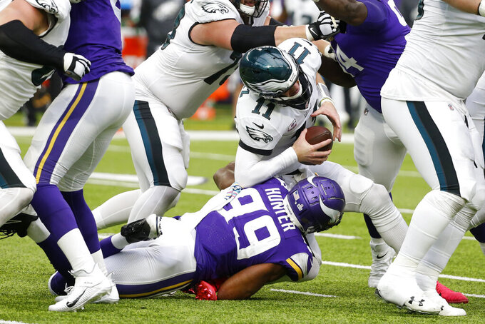 Philadelphia Eagles quarterback Carson Wentz (11) is sacked by Minnesota Vikings defensive end Danielle Hunter (99) during the second half of an NFL football game, Sunday, Oct. 13, 2019, in Minneapolis. (AP Photo/Bruce Kluckhohn)