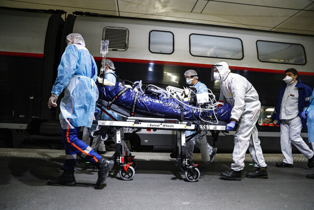 Medical staff embark a patient infected with the COVID-19 virus in a train at the Gare d'Austerlitz train station Wednesday April 1, 2020 in Paris. France is evacuating 36 patients infected with the coronavirus from the Paris region onboard two medicalized high-speed TGV trains. The patients, all treated in intensive care units (ICU), are being transferred to several hospitals in Britany, as western France is less impacted by the epidemic. The new coronavirus causes mild or moderate symptoms for most people, but for some, especially older adults and people with existing health problems, it can cause more severe illness or death. (Thomas Samson, Pool via AP)