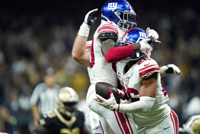 New York Giants running back Saquon Barkley (26) celebrates his touchdown in overtime with wide receiver Kadarius Toney to defeat the New Orleans Saints 27-21, during an NFL football game in New Orleans, Sunday, Oct. 3, 2021. (AP Photo/Brett Duke)