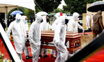 In this photo provided by the South African Government Communications and Information Services (GCIS) pallbearers carry the coffin in Witbank, South Africa, Sunday, Jan. 24, 2021, at the funeral of Cabinet minister Jackson Mthembu, who died of COVID-19 last week. Police are investigating the premier of the Mpumalanga province Refilwe Mtsweni-Tsipane for failing to wear a mask and for hugging a police officer at the public funeral. (Kopano Tlape/South African Government Communication and Information Services via AP)