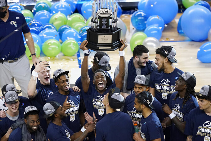 Georgia Tech players hold the trophy as they celebrate their 80-75 win over Florida State in the Championship game of the Atlantic Coast Conference tournament in Greensboro, N.C., Saturday, March 13, 2021. (AP Photo/Gerry Broome)