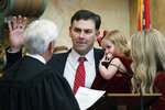 Secretary of State Michael Watson holds his youngest daughter, Cora Elizabeth, 18 months, as he is sworn into office by Mississippi Supreme Court Chief Justice Michael Randolph, left, in House chambers at the Mississippi Capitol in Jackson, Miss., Thursday, Jan. 9, 2020. (AP Photo/Rogelio V. Solis)