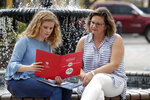 In this Friday, April 10, 2020, photo in Sanford, Fla., Serra Sowers, left, and her mother Ebru Ural look over brochures from various colleges. The coronavirus pandemic has changed the process of college visits to online and virtual interviews. (AP Photo/John Raoux)