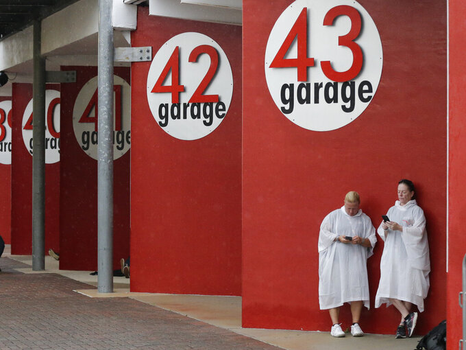 Race fans seek shelter in the garage area during a rain shower before a NASCAR Xfinity Series auto race at Daytona International Speedway, Friday, July 5, 2019, in Daytona Beach, Fla. (AP Photo/Terry Renna)