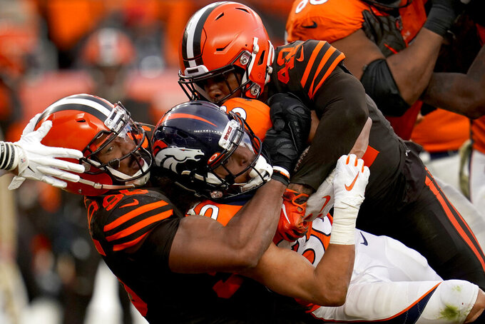 FILE - In this Nov. 3, 2019, file photo, Denver Broncos running back Phillip Lindsay, center, is tackled by Cleveland Browns defensive tackle Sheldon Richardson, left, during the second half of NFL football game in Denver. No piece of protective equipment has undergone as much transformation over the past decade as the helmet. (AP Photo/Jack Dempsey, File)