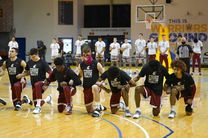 Washington State players kneel during the national anthem in front of standing Stanford players before an NCAA college basketball game in Santa Cruz, Calif., Saturday, Jan. 9, 2021. (AP Photo/Jeff Chiu)