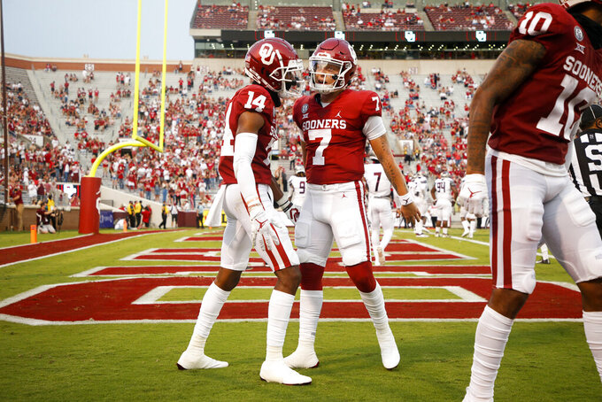 Oklahoma wide receiver Charleston Rambo (14) and quarterback Spencer Rattler (7) celebrate after Rambo's touchdown catch during an NCAA college football game against Missouri State in Norman, Okla., Saturday, Sept. 12, 2020. (Ian Maule/Tulsa World via AP)
