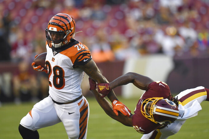 Cincinnati Bengals running back Joe Mixon (28) runs past Washington Redskins cornerback Josh Norman, right, during the first quarter of an NFL preseason football game in Landover, Md., Thursday, Aug. 15, 2019. (AP Photo/Susan Walsh)