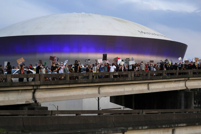 Protesters take over the elevated Interstate 10 during a march in New Orleans, Tuesday, June 2, 2020, protesting the death of George Floyd, who died May 25 in Minneapolis after being restrained by police. In the background is the Superdome. (AP Photo/Gerald Herbert)