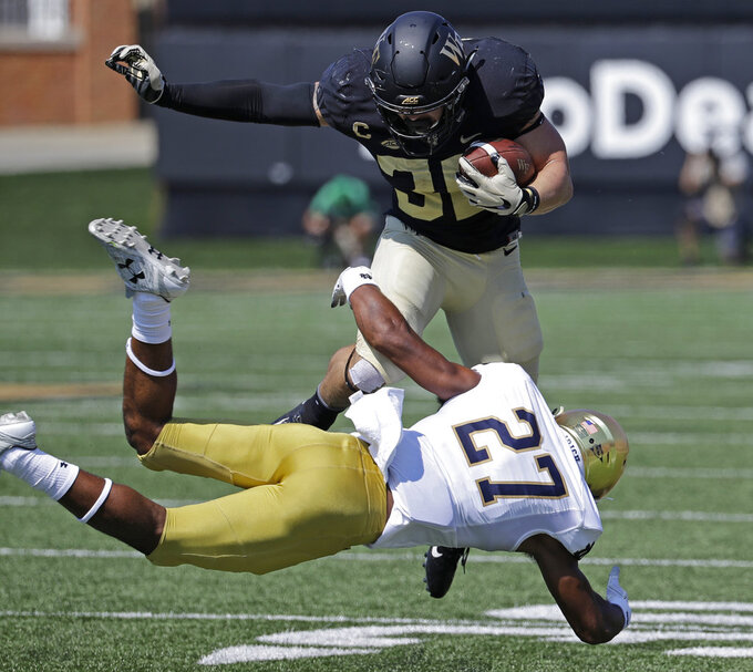 FILE - In this Sept. 22, 2018, file photo, Wake Forest's Cade Carney (36) is tackled by Notre Dame's Julian Love (27) in the first half of an NCAA college football game, in Winston-Salem, N.C. Love was named to The Associated Press Midseason All-America team, Tuesday, Oct. 16, 2018. (AP Photo/Chuck Burton, File)